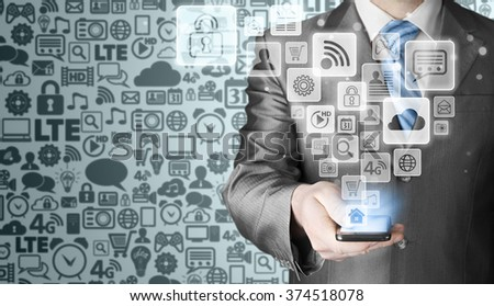 Business man using smart phone with social media icon set - stock photo