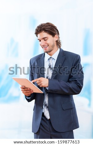 business man using tablet pad computer in bright blue office, touch screen young businessman