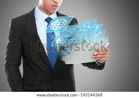 Business man using tablet PC and smiling with conceptual image - stock photo