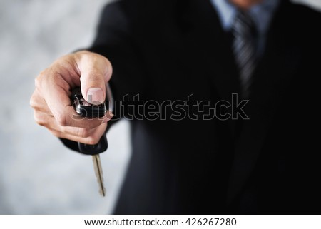 Business man using the key to open a car transportation and ownership concept. - stock photo