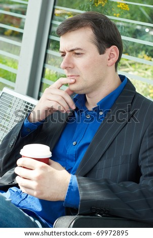 business man wait for a bus with a cup of coffee - stock photo