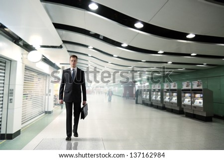 business man walking in subway - stock photo