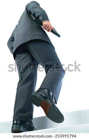 Business man walking up stairs to a customer meeting carrying documents shot from low angle to make more dynamic - stock photo