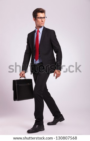 business man walking with a briefcase and looking away, on gray - stock photo