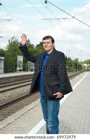 Business man waving a train - stock photo