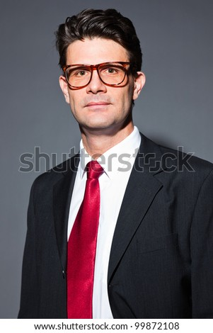 Business man wearing retro glasses with blue suit and red tie isolated on dark background. Serious looking. Studio shot.
