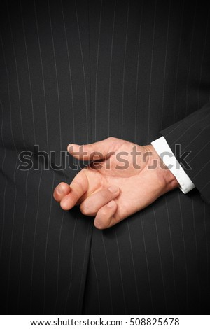 Business man wearing suit with fingers crossed behind back