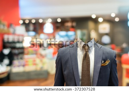 Business man wearing suit without head with coffee shop on background - stock photo