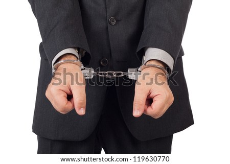 business man with a black suit in handcuffs, front view - stock photo