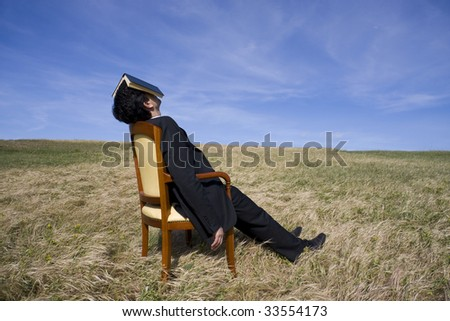 Business man with a book on his head having a rest on the nature