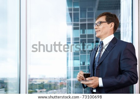 Business man with a cup of coffee in the office - stock photo