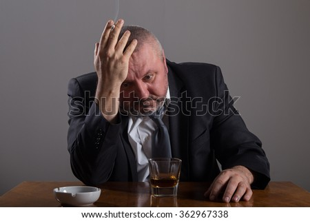 Business man with a glass of whiskey and cigarette - stock photo