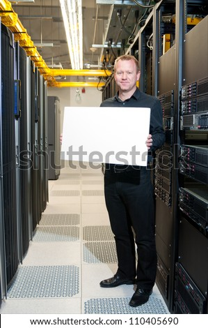 Business man with a satisfied look holding a white board in a datacenter. - stock photo