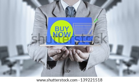 business man with an open hand as showing buy now on laptop computer with cart as concept - stock photo