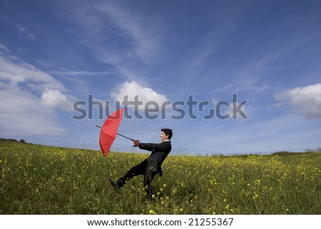 Business man with an open umbrella on the field - stock photo