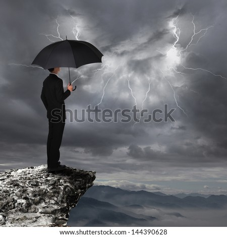 Business Man with an umbrella look rainstorm clouds and lightning over danger precipice on the mountain. - stock photo