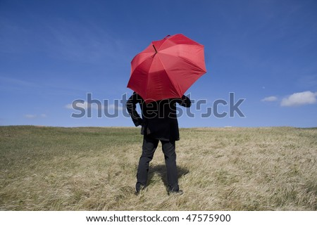 Business man with an umbrella on the meadow - stock photo