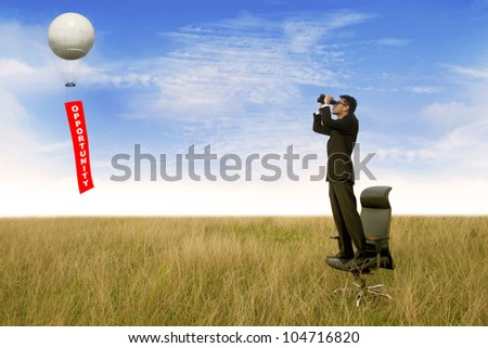 Business man with binoculars looking for an opportunity - stock photo