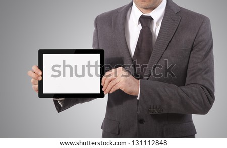 business man with blank touch tablet in hands, grey background - stock photo