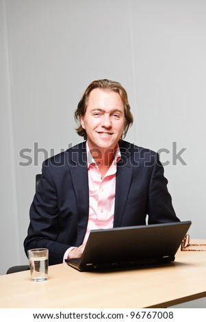 Business man with blond hair working with laptop computer sitting behind desk in office isolated on white background. Wearing pink shirt and blue suit.