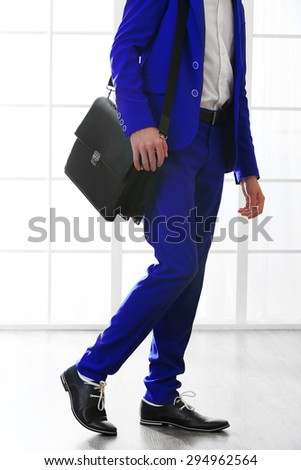 Business man with briefcase on bright background - stock photo