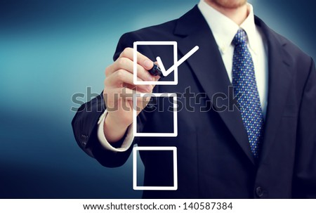 Business man with checkboxes over blue background - stock photo