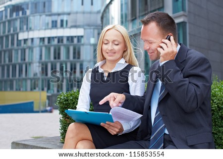 Business man with contract and smartphone sitting near a business woman - stock photo