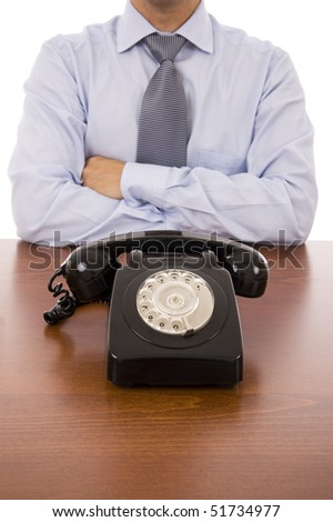Business man with crossed arms waiting for a call