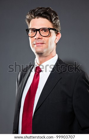 Business man with dark grey suit and red tie isolated on dark background. Wearing vintage glasses. Studio shot.