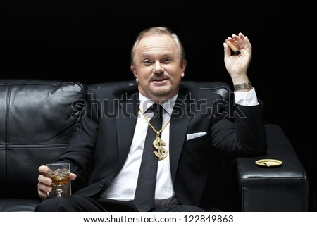 Business man with drink and cigarette sitting on the black sofa