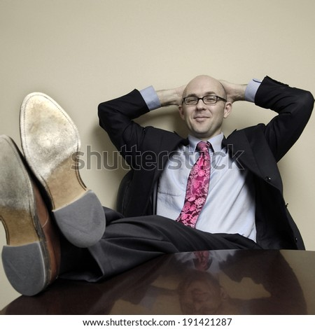 Business man with feet on at table relaxing in office