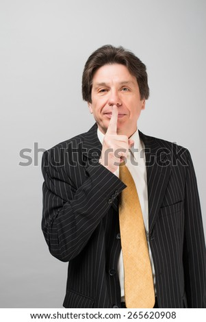 Business man with finger on lips asking for silence over gray background - stock photo