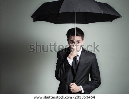 Business man with funny expression holding an umbrella.  - stock photo