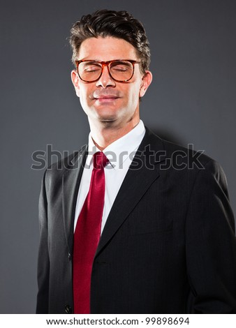 Business man with grey suit and red tie isolated on dark background. Wearing retro glasses. Studio shot.