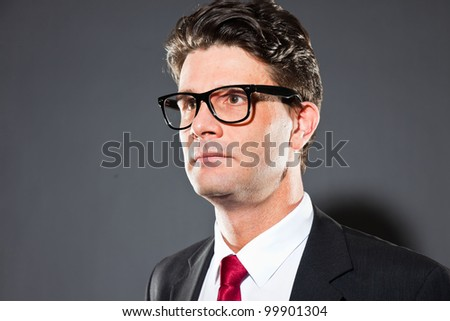 Business man with grey suit and red tie isolated on dark background. Wearing vintage glasses. Studio shot.