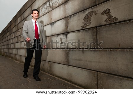Business man with grey suit and red tie walking on the street near brick wall. Industrial environment.