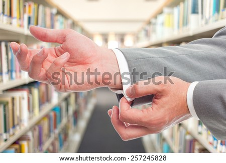 Business man with grey suit, he is tying his shirt. Over library background - stock photo