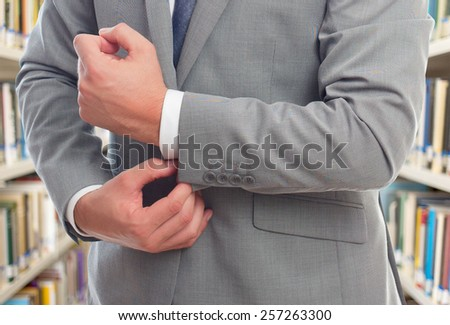 Business man with grey suit. He is tying his shirt. Over library background - stock photo