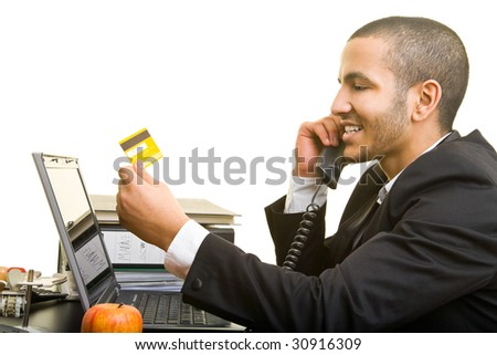 Business man with his laptop and a credit card on the phone - stock photo