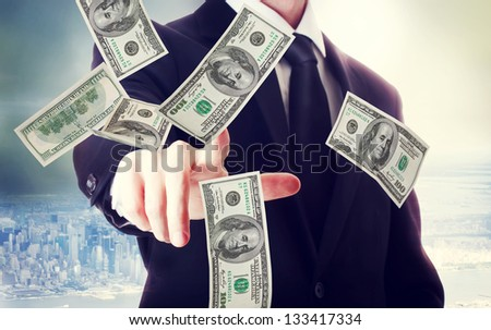 Business man with hundred dollar bills on big city backdrop - stock photo
