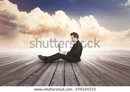 business man with laptop on wooden floor - stock photo