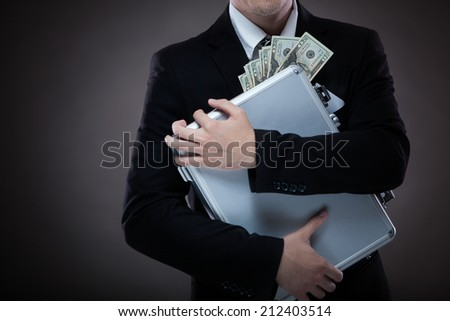 Business man with metal suitcase full of money - stock photo