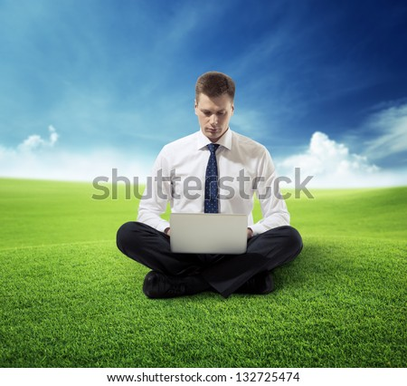 business man with notebook sitting on grass - stock photo