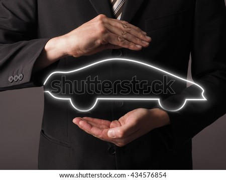 Business man with protecting hands and a car silhouette