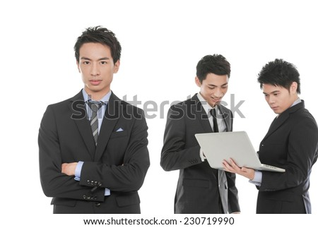 Business man with talking colleagues behind her against a white background - stock photo