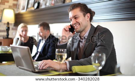 Business man with the laptop sits at a table in cafe