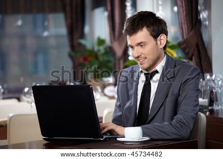 Business man with the laptop sits at a table in cafe - stock photo