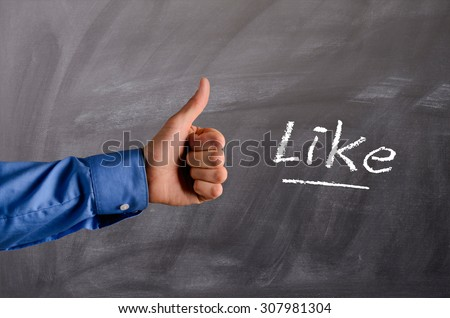Business man with thumb up on a blackboard - stock photo