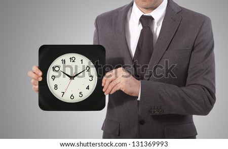 business man with wall clock on his hand, grey background