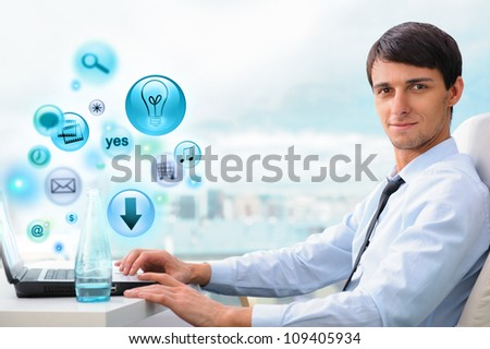 Business man working at his office using laptop and different icons appearing from the screen - stock photo